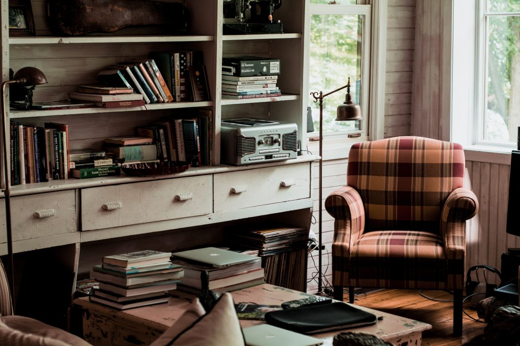 A comfortable home office with books, a reading chair and lamp, and windows for natural light.