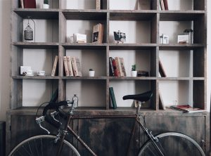 A wall bookshelf with equal-sized shelves holds books and art while a bike leans against it.