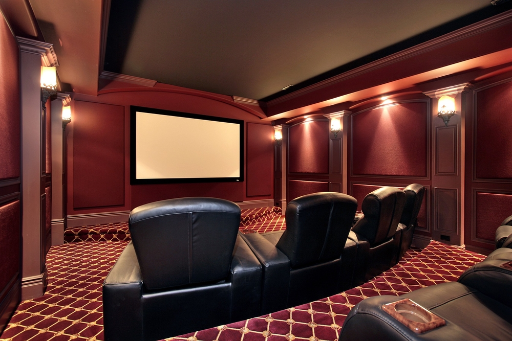 A home theater is decorated with red and gold accents and black arm chairs.