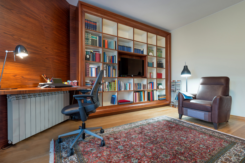 A home office has a oriental rug, a desk and chairs, and a wall-sized bookshelf with a TV in the middle.