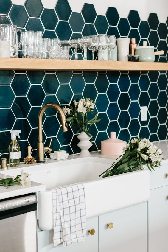 A beautiful modern kitchen sink area with blue tiled walls and flowers in the sink.