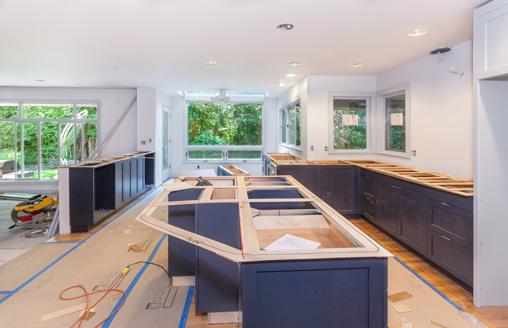 A kitchen in the middle of a remodel with blank floors and measured countertops.